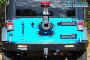Rear end view of a sky blue JK Jeep Wrangler Wagon fitted with a new Kaymar rear bar and spare tyre relocation kit