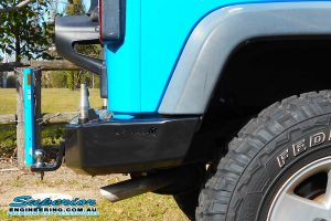 Right side closeup view of a sky blue JK Jeep Wrangler Wagon fitted with a new Kaymar rear bar and spare tyre relocation kit