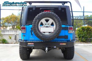 Full rear end view of a sky blue JK Jeep Wrangler Wagon fitted with a new Kaymar rear bar and spare tyre relocation kit at the Superior 4x4 Retail Showroom