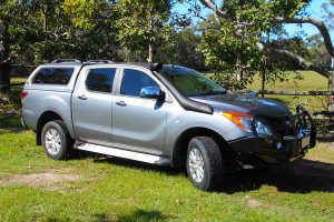 Right side view of a silver Mazda BT-50 (Dual Cab) fitted with an Ironman 4x4 Deluxe Commercial Bullbar, Ute Canopy and TJM Airtec Snorkel