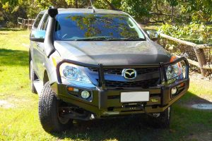 Front view of a silver Mazda BT-50 (Dual Cab) showing the Ironman 4x4 Deluxe Commercial Bullbar and TJM Airtec Snorkel