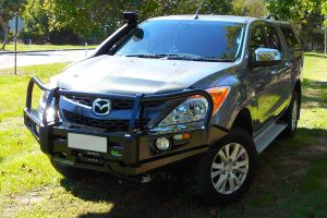 Front right view of a Mazda BT-50 (Dual Cab) showing off the Ironman 4x4 Deluxe Commercial Bullbar and TJM Airtec Snorkel fitted by Superior
