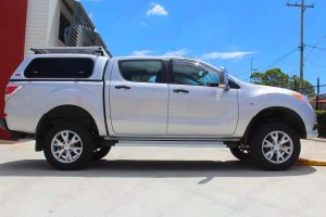 Right side view of a silver dual cab Mazda BT-50 after being fitted with a 2 inch lift kit at the Superior Engineering Deception Bay workshop