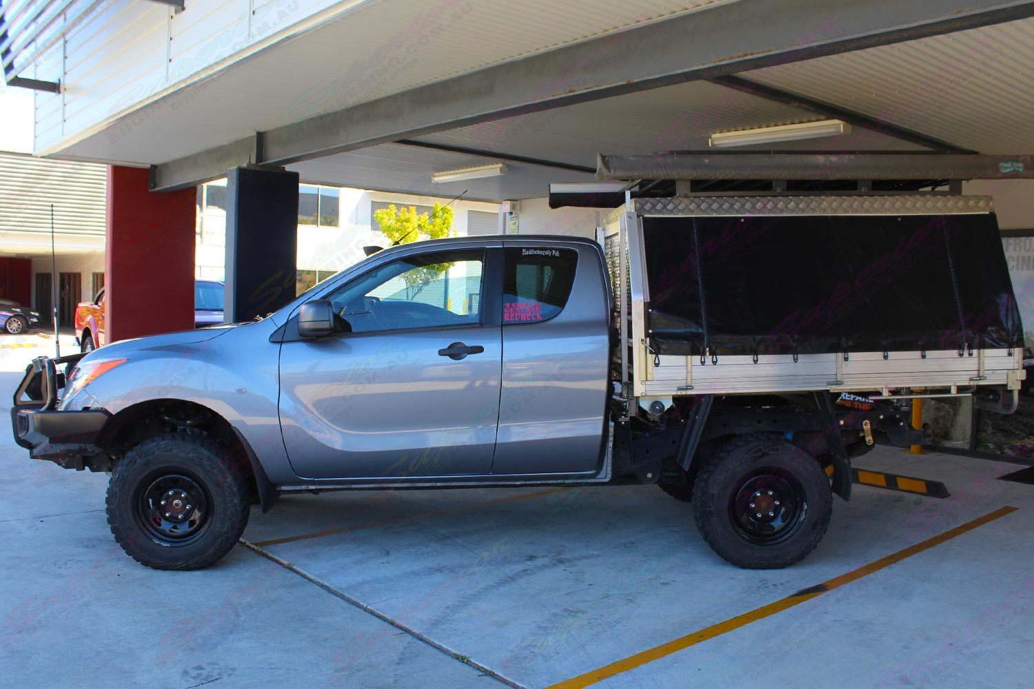 Left side view of a grey extra cab Mazda BT-50 after being fitted with a 2 inch Bilstein lift kit at the Superior Engineering workshop