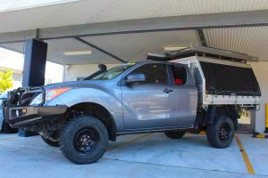 Front left view of a grey extra cab Mazda BT-50 after being fitted with a 2 inch Bilstein lift kit at the Superior Engineering workshop