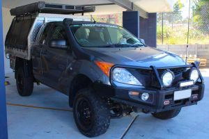 Front right view of a grey extra cab Mazda BT-50 after being fitted with a 2 inch Bilstein lift kit out the front of the Superior Engineering 4x4 showroom