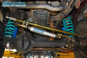 Closeup under vehicle view of a SWB Patrol fitted with a Superior steering damper, comp spec draglink, panhard rod and a pair of blue coil springs