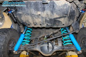Closeup under vehicle view of a pair of blue coil springs, superior remote reservoir shock absorbers and a brake proportioning valve bracket fitted to the SWB Patrol