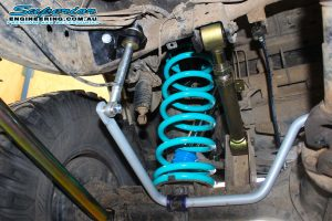 Closeup under vehicle view of a single blue coil spring, superior superflex swaybar, adjustable upper control arm and a swaybar extension fitted to the SWB GQ Nissan Patrol