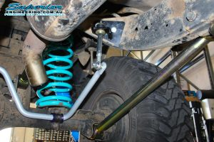 Closeup under vehicle view of a single blue coil spring, superior superflex swaybar, fixed lower control arm and a swaybar extension fitted to the SWB GQ Nissan Patrol