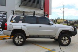 Right side view of a silver GU Nissan Patrol Wagon at the Deception Bay 4x4 showroom after fitting a 4 inch Superior Remote Reservoir Drop Box Lift Kit