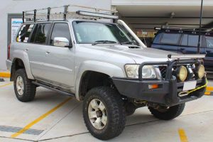 Front right view of a silver GU Nissan Patrol Wagon at the Deception Bay 4x4 workshop after fitting a 4 inch Superior Remote Reservoir Drop Box Lift Kit