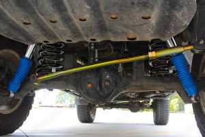 Closeup under vehicle view of the superior panhard rod, black coil springs and remote res shocks fitted to the GU Nissan Patrol Wagon