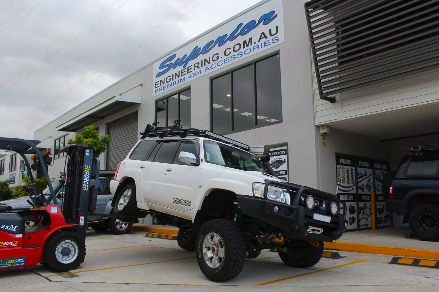 Front right view of a GU Nissan Patrol Wagon testing out the rear flex on the forklift after being fitted with a Superior Remote Reservoir Hybrid Superflex 4 Inch Lift Kit