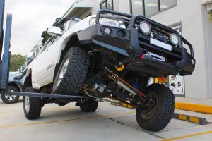 Front view of a white GU Nissan Patrol Wagon testing out the front flex using the forklift after being fitted with a 4 inch Superior Remote Reservoir Hybrid Superflex Lift Kit at the Deception Bay 4x4 Workshop