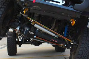 Closeup under vehicle view of the draglink, front diff guard, coil springs and shocks fitted to a GU Nissan Patrol wagon
