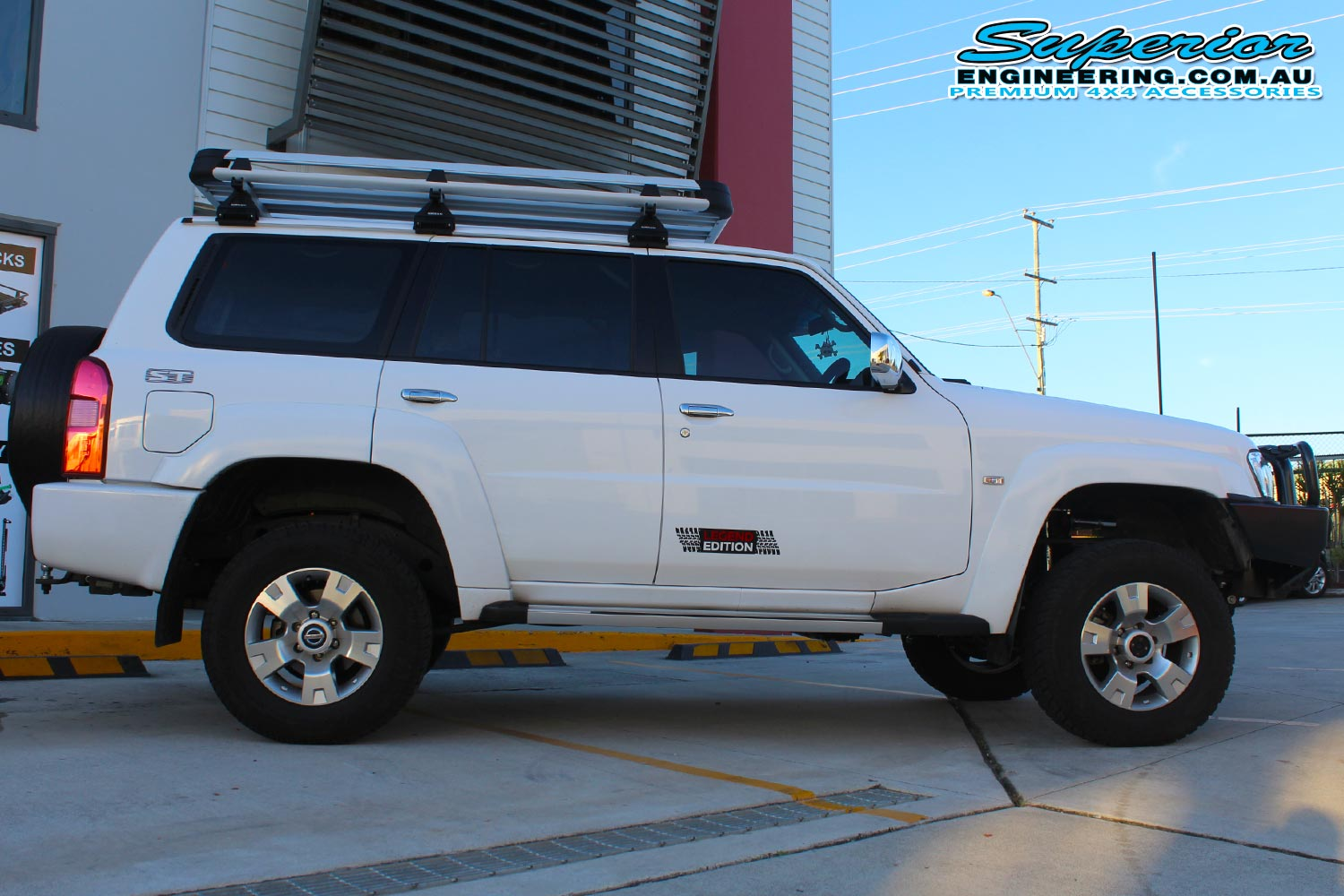 Right side view of a GU Nissan Patrol after installing a 2 Inch Superior Remote Reservoir Lift Kit and coil tower brace