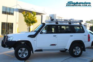 Left side view of a white GU Nissan Patrol wagon after installing a 2 Inch Superior Remote Reservoir Lift Kit and coil tower brace kit at the Deception Bay 4x4 Retail Showroom