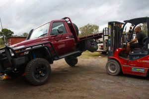 Front left view of the Maroon 79 Series Toyota Landcruiser (Single Cab) testing out the flex of the rear coil conversion kit using the forklift at the Superior warehouse
