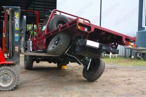 Rear end view of the 79 Series Toyota Landcruiser (Single Cab) testing out the flex of the rear coil conversion kit using the forklift at the Superior warehouse