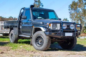 Front right view of a Grey 79 Series Single Cab Toyota Landcruiser at Superior Engineering fitted out with a rear coil conversion kit and front suspension kit