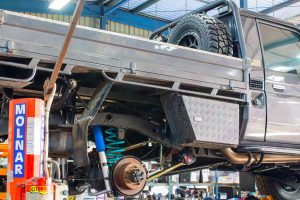 A 79 Series Single Cab Toyota Landcruiser on the hoist at Superior Engineering's Burpengary workshop getting the 2 inch coil conversion kit fitted