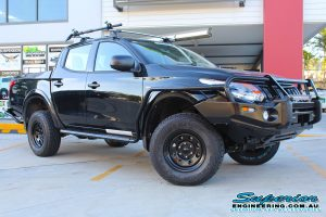 Front right view of a black Mitsubishi MQ Triton fitted with a 40mm Bilstein lift kit and a full range of Ironman 4x4 Accessories