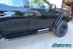 Right side view of a MQ Mitsubishi Triton dual cab fitted with an Ironman 4x4 steel side steps and brush bar rails