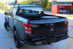 Full rear end view of a MQ Mitsubishi Triton dual cab fitted with an Ironman 4x4 steel side steps, side rails, awning and rear protection bar at the DBay 4WD retail store