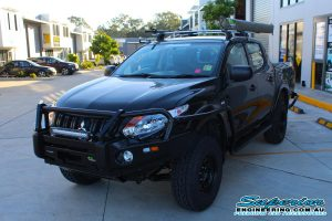 Left front view of a MQ Mitsubishi Triton dual cab fitted with an Ironman 4x4 black deluxe commercial bullbar, side steps, side rails and awning at the Deception Bay 4WD retail store