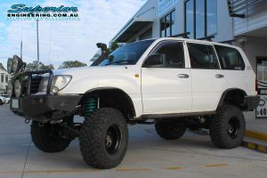 Left side view of a white 105 Series Toyota Landcruiser 4wd fitted with the huge 6 inch lift kit by Superior Engineering