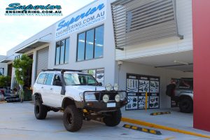 Front right view of a white 105 Series Toyota Landcruiser wagon fitted with the huge 6 inch superflex lift kit at the Superior Engineering 4x4 Retail showroom