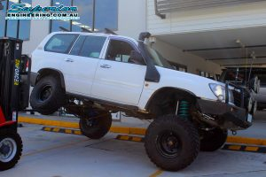 Flexing the rear drivers side of the 105 Series Toyota Landcruiser to test the suspension after being fitted with the huge 6 inch superflex lift kit at the Superior Engineering 4x4 Retail showroom