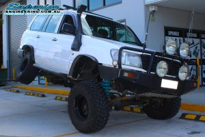 Flexing the rear drivers side of the 105 Series Toyota Landcruiser to test the suspension after being fitted with a 6 inch SuperFlex lift kit at the Superior Engineering 4x4 Retail showroom