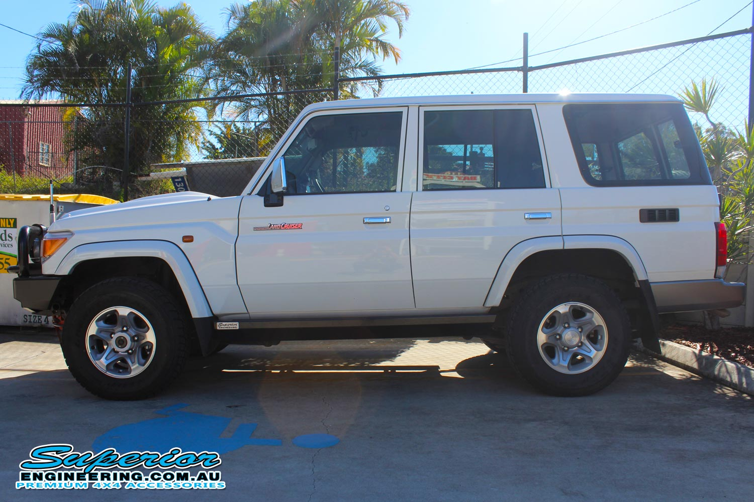 Left side view of a white 76 Series Toyota Landcruiser after being fitted with a Superior engine guard and a set of rock sliders