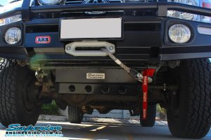 Closeup underside view a Superior radiator and engine guard fitted to the front of a 76 Series Toyota Landcruiser four wheel drive