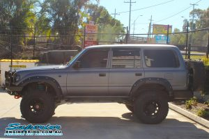 Left side view of a 80 Series Toyota Landcruiser fitted with a set of Dobinsons coil springs out the front of the Deception Bay 4wd retail showroom