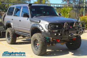 Front right view of an 80 Series Toyota Landcruiser wagon fitted with a set of heavy duty Dobinsons coil springs out the front of the Deception Bay 4wd retail showroom