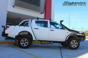 Right side view of a white Mitsubishi Triton four wheel drive after being fitted with a 20mm Bilstein lift kit and a full range of 4x4 accessories from Superior Engineering