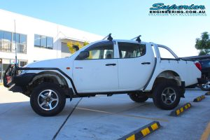 Left side view of a white Mitsubishi Triton four wheel drive after being fitted with a 20mm Bilstein lift kit and a full range of 4x4 accessories from Superior Engineering
