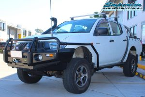 Front view of a white Mitsubishi Triton four wheel drive after being fitted with a 20mm Bilstein lift kit, side rails, bullbar, snorkel and underbody guard