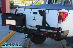 Right rear view of a white Mitsubishi Triton four wheel drive fitted with a MCC4x4 Rear Bar with Wheel Carrier and Dual Jerry Can Holder