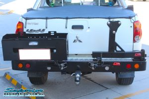Full rear end view of a white Mitsubishi Triton four wheel drive fitted with a MCC4x4 Rear Bar with Wheel Carrier and Dual Jerry Can Holder