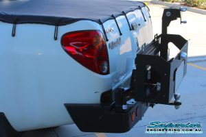 Left end view of a MCC 4x4 Rear Bar with Wheel Carrier and Dual Jerry Can Holder fitted to a white Mitsubishi Triton four wheel drive vehicle