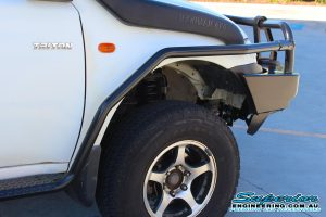 Front right closeup view of a Ironman 4x4 Side Rails and Deluxe Black Commercial Bull Bar fitted to a dual cab Mitsubishi Triton four wheel drive vehicle