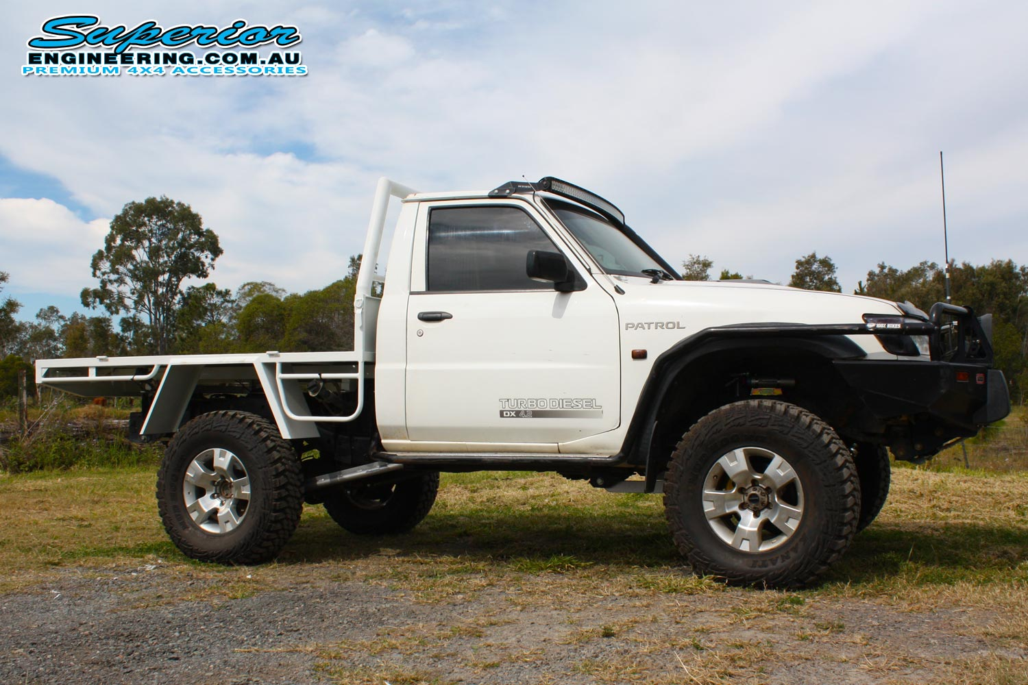 Right side view of a white GU Nissan Patrol ute after being fitted with a complete Superior Engineering 4x4 accessory and suspension fitout