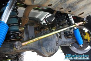 Closeup view of a single heavy duty rear Superior panhard rod, pair of black coil springs and remote reservoir shocks fitted to the rear of the GU Nissan Patrol Ute
