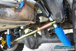 Closeup view of a single heavy duty rear Superior panhard rod, pair of remote reservoir shocks and rubber bumpstop fitted to the rear of the GU Nissan Patrol Ute