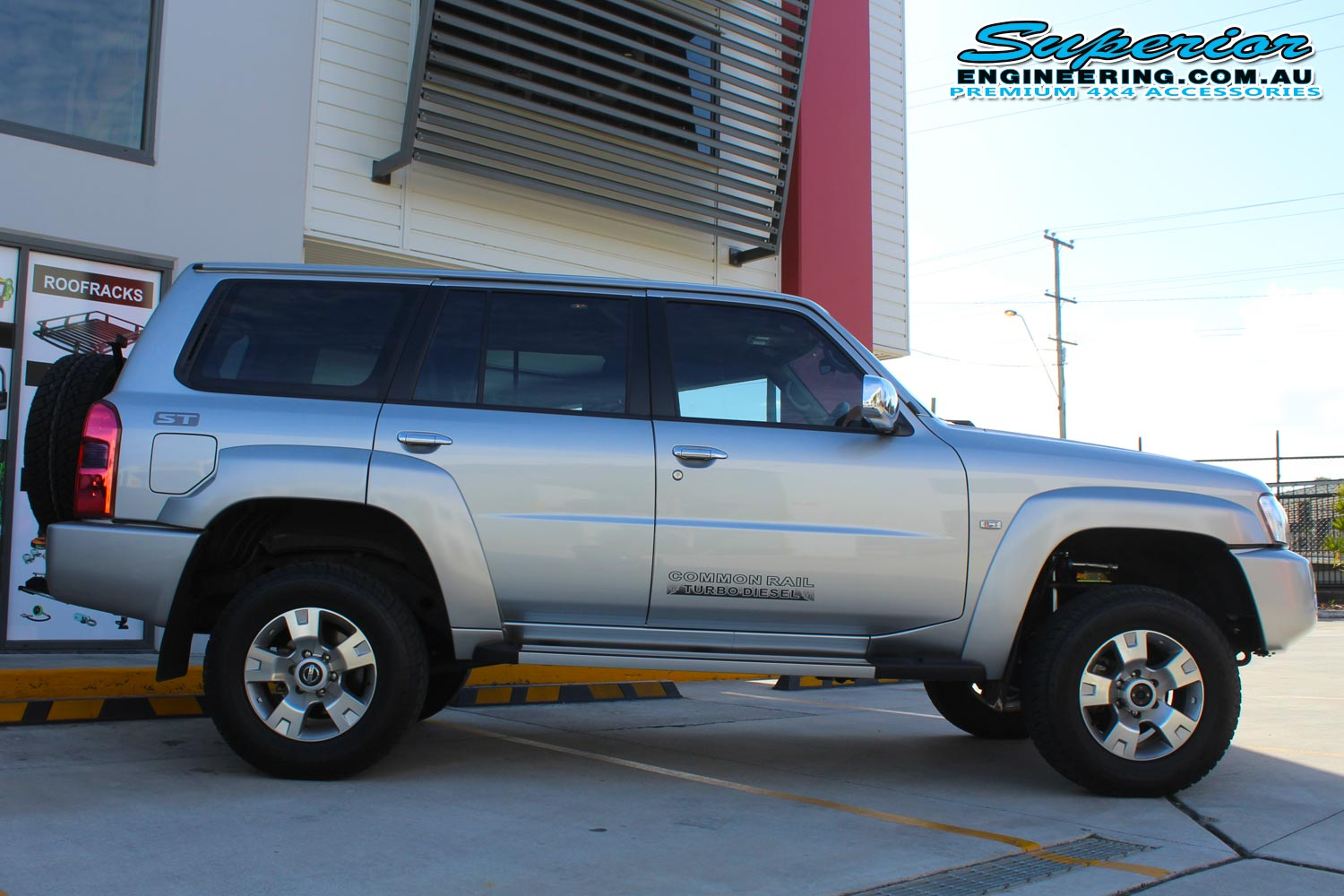 Right side view of a silver GU Nissan Patrol wagon fitted with a top of the range 2 inch Superior Remote Reservoir Lift Kit
