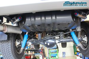 Closeup view of a pair of black Superior coil springs and remote reservoir shocks fitted to the rear of a Nissan Patrol on the hoist at the Deception Bay 4x4 retail showroom
